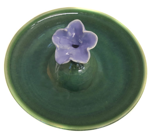 "A gorgeous cat fountain in a Petunia design with a Lavender Blue blossom and a Deep Spruce fountain bowl. Water fills the blossom and streams into the bowl. Excellent for long hair cats. * 3.25 inches high by 12"" in diameter at the widest * 8 cup capacity * 100% food-safe & tested ceramics * Pleasant water sounds or quiet, as you choose * Very easy to clean * Can be adapted for use in EU outlets. European pumps can be purchased via the following link: https://www.etsy.com/listing/384659996/installation-of-european-2202140v-pump?ga_search_query=EU&ref=shop_items_search_18 This fountain does not take any of the Cat Taps , the Serenity flow or the copper Waterleaf. What is included:"